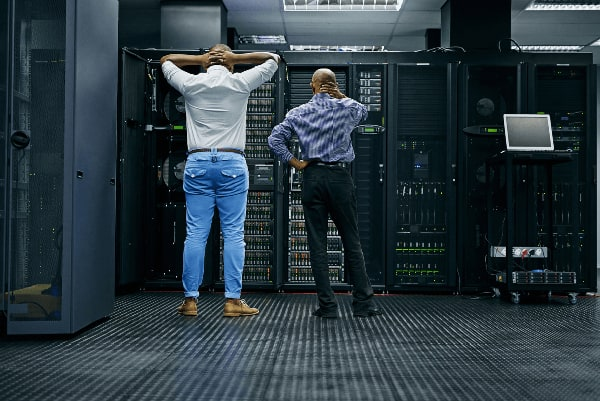 Two engineers confused in front of server stack
