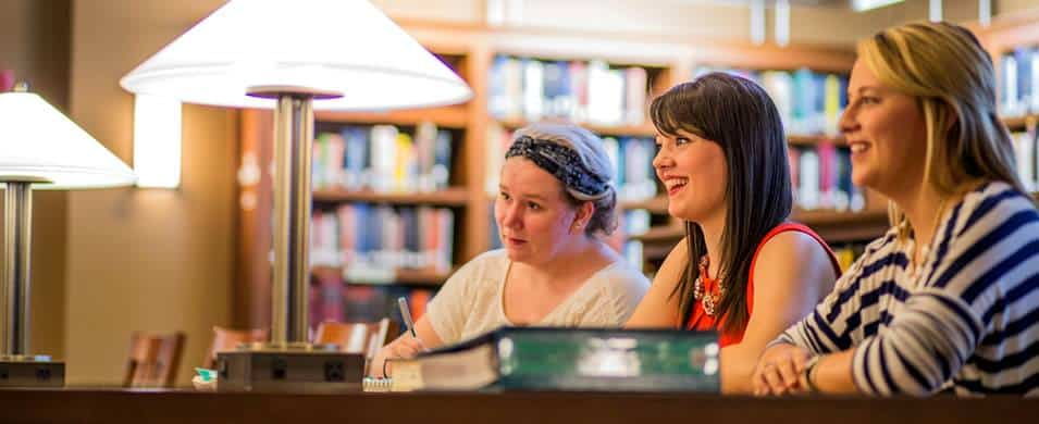Three women working in the library together